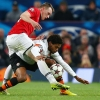 Manchester United's Phil Jones [L] in action with Shakhtar Donetsk's Luiz Adriano during their UEFA Champions League Group Stage match at Old Trafford on December 10, 2013