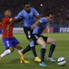 Diego Godín (R) and Álvaro Pereira (C) of Uruguay compete for a ball with Eduardo Vargas (L) of Chile during their friendly match on 18th November, 2014