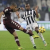 Juventus' Patrice Evra (R) fights for the ball with Torino's Bruno Peres during their Serie A match at Juventus Stadium on 30th November, 2014